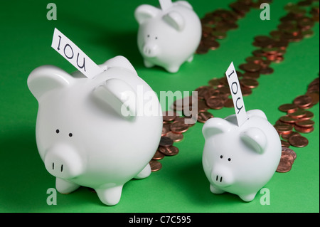 Piggy Bank's with IOU's coming out of coin slots and money coming out of piggy banks - Stock Photo