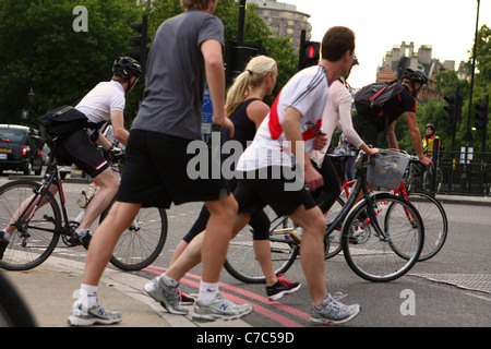 cyclists and joggers ignoring traffic lights and crossing the road at Hyde Park Corner during an evening rush hour - Stock Photo