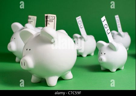Piggy banks with IOU's and money coming out of coin slots - Stock Photo