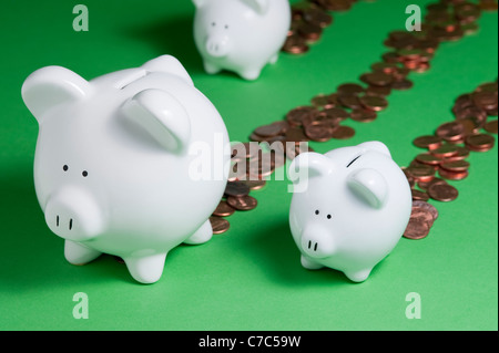Group of Piggy Banks leaking pennies out back end losing money and savings - Stock Photo