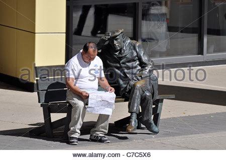 Man sitting on bench beside Glenn Gould Statue outside Glenn Gould Studio, Toronto, Canada - Stock Photo