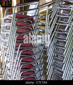 Three stacks of red, violet, and yellow seat stainless steel chairs nex to a restaurant - Stock Photo