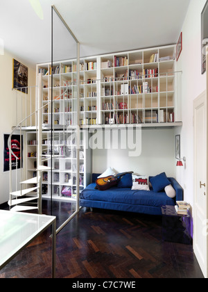 modern bedroom with wood floor and bookcase above bed - Stock Photo