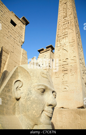 Head from the Colossal Seated Statue of Ramses II and the obelisk at the first pylon of Luxor Temple, Luxor, Egypt - Stock Photo