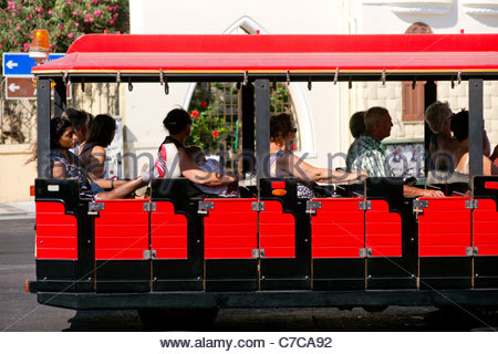 Tourists sightseeing in Rhodes Greece riding a red mini train looking at the sights - Stock Photo