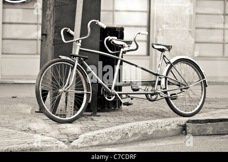 An old two seater bike parked on the streets - Stock Photo