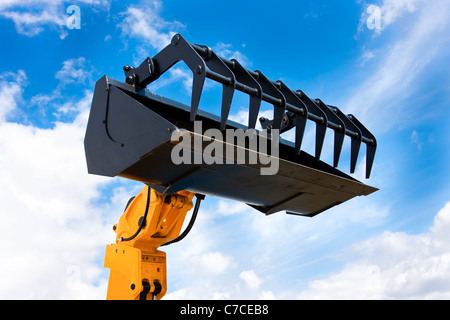 Yellow Hydraulic Excavator Black Grab Bucket Isolated Against Blue Sky - Stock Photo