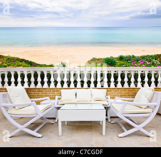 Patio with white wicker furniture with view of Mediterranean beach in Greece - Stock Photo