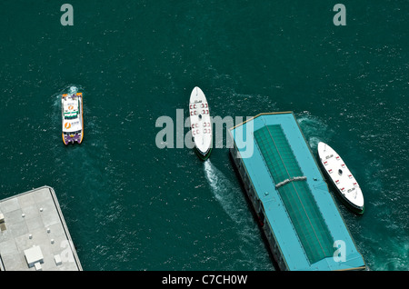 Aerial view of a ferry pier and a departing Star Ferry from the rooftop of IFC 2, in Central Hong Kong. - Stock Photo