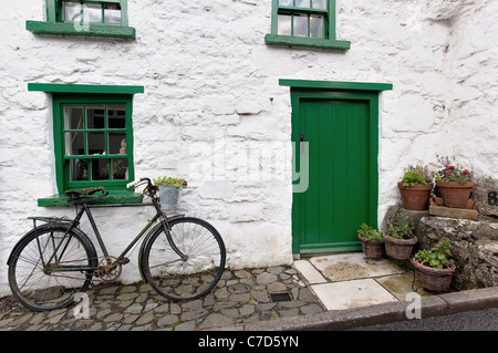 Bicycle leaning against a row of cottages in Glenoe, Co Antrim - Stock Photo