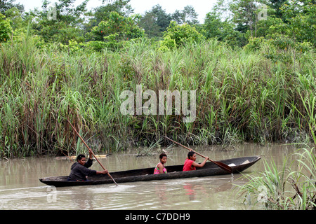 Three girls in a dugout canoe on a river in Papua New Guinea - Stock Photo