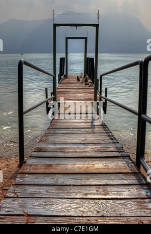 lonely boat dock on Lake Lugano with ducks - Stock Photo