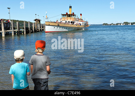 Children on foreshore watching a Chiemsee Ferry Boat at the Herreninsel, Chiemgau Upper Bavaria Germany - Stock Photo