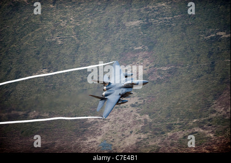 USAF F-15E Strike Eagle makes a turn during a low flying flight in mid Wales shot from the hill side - Stock Photo