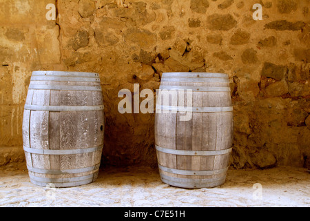 barrels of wine built in oak wood from Spain on stone masonry wall - Stock Photo