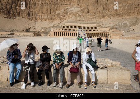 Japanese tourists wearing surgical face masks at the Temple of Hatshepsut, Luxor, Egypt - Stock Photo