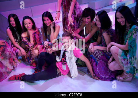 Chinese fashion models with a foreign staff in Beijing, China. 18-Sep-2011 - Stock Photo