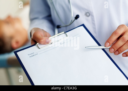Hand of female doctor with pen pointing at clipboard - Stock Photo