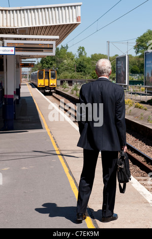 Businessman waiting on a railway station platform as a train approaches. - Stock Photo