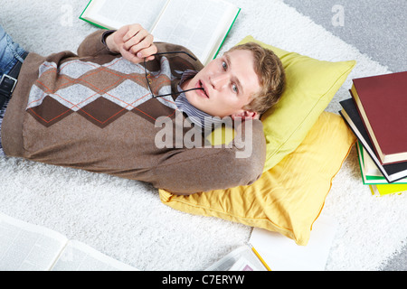 Image of serious student lying on the floor and doing homework - Stock Photo