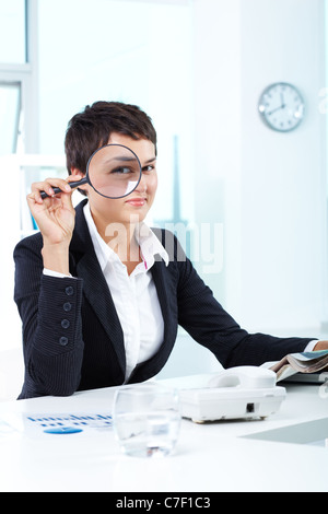 Photo of pretty businesswoman looking at camera through spy glass - Stock Photo
