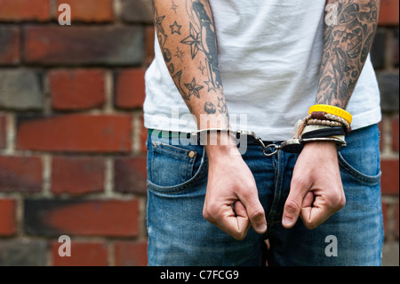 Handcuffed teenager with tattoos - Stock Photo