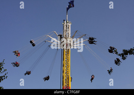 people whirling around on a funfair ride called the star flyer on the embankment of the River Thames - Stock Photo