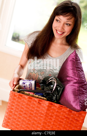 Girl unpacking box of goods - Stock Photo