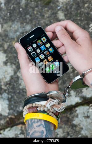Handcuffed teenager holding an Apple iphone. - Stock Photo