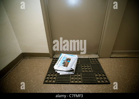 A home delivery copy of the New York Times in front of a door in an apartment building in New York - Stock Photo