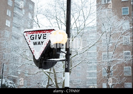 Give Way road sign covered in snow, London December 2011, England, UK - Stock Photo