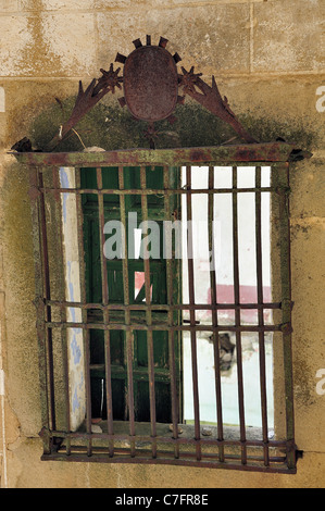 old broken window with grid in a yellow brick wall - Stock Photo