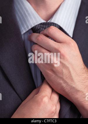 Businessman adjusting his tie. Closeup of hands. - Stock Photo