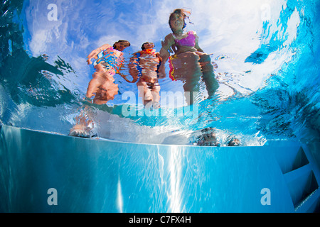 Children on the side of an open air swimming pool (Bellerive-sur-Allier - France). Underwater view. - Stock Photo