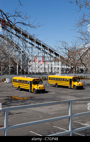 Two empty school buses in an abandoned parking lot, Coney Island, USA - Stock Photo