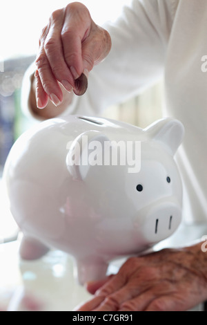 Detail of a senior woman putting a coin into a piggy bank - Stock Photo