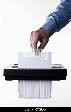 A man feeding a blank document into a paper shredder, close-up - Stock Photo