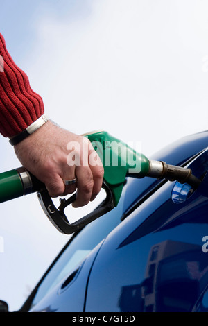 Hand and gas pump nozzle refueling car with unleaded gas. - Stock Photo