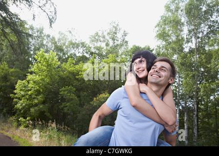 A man giving his girlfriend a piggyback ride through a field - Stock Photo