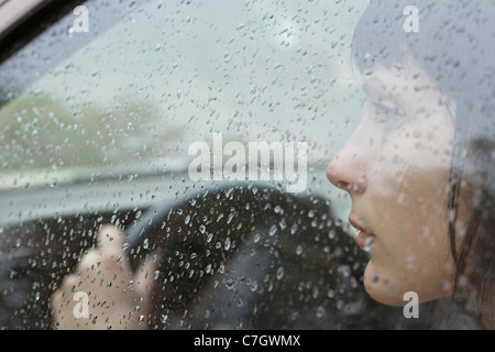 A woman driver sitting in car looking out window, raindrops on window - Stock Photo
