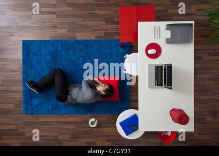 A businessman sleeping on a rug near his desk, overhead view - Stock Photo