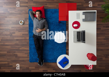 A man lying on a rug next to his home office desk, overhead view - Stock Photo