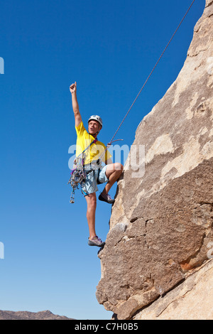 Male rock climber celebrates after a successful ascent. - Stock Photo