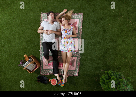 A couple napping on a blanket in a park, overhead view - Stock Photo