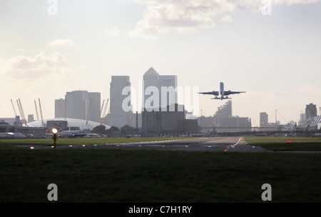 passenger aircraft taking off from London City airport with docklands city of London and the O2 dome in the background - Stock Photo
