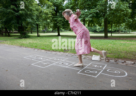 Senior woman playing hopscotch - Stock Photo