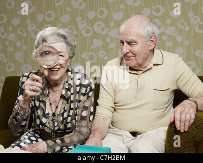 Senior man amused as senior woman magnifies appearance of her eye with magnifying glass - Stock Photo