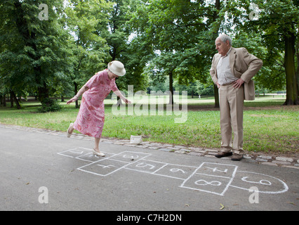 Senior couple play hopscotch - Stock Photo