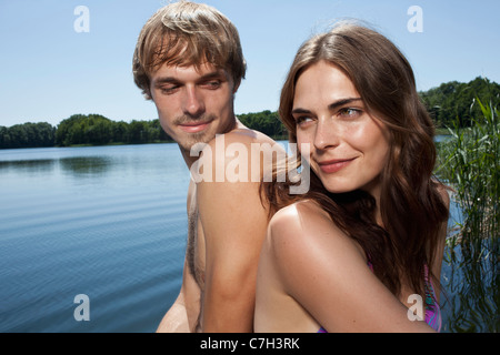 Couple back to back beside the lake - Stock Photo