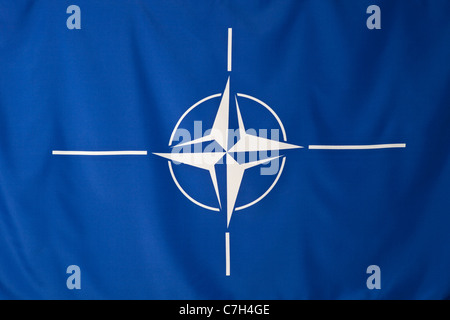 North Atlantic Treaty Organization flag, white compass rose emblem in blue background - Stock Photo